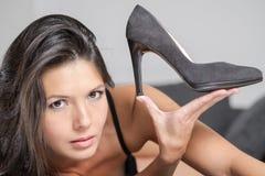 阻止一双典雅的鞋子的可爱的妇女 免版税库存图片