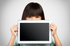 阻止一台空白的片剂计算机的小女孩遮暗低落 免版税库存照片