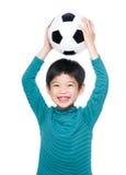 阻止与足球的亚洲小男孩 库存图片