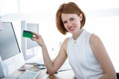 阻止信用卡的微笑的行家女商人 免版税库存图片