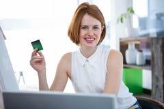 阻止信用卡的微笑的行家女商人 免版税库存照片