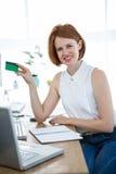 阻止信用卡的微笑的行家女商人 库存照片