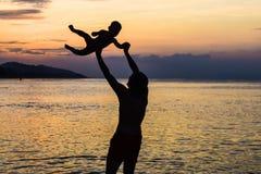 阻止在他的年轻愉快的父亲武装举起他的小儿子在海滩在海波浪湿sa前面的赤足身分 免版税库存图片