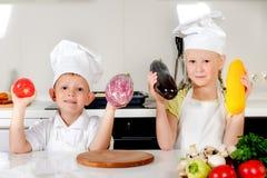 阻止新鲜蔬菜的两个微笑的孩子 免版税库存照片