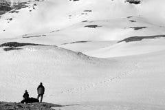 止步不前的两个远足者在多雪的山 免版税图库摄影