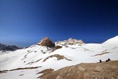 止步不前的两个远足者在多雪的山 免版税库存图片