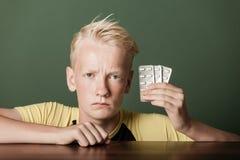 阻止药片的皱眉头的十几岁的男孩 免版税库存照片