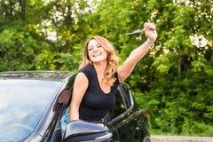 阻止钥匙的年轻快乐的快乐的微笑的华美的妇女对她的第一辆新的汽车 用户满意 免版税图库摄影