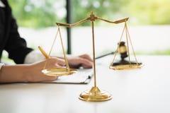 正义标度在白色桌背景的与工作在律师事务所的女性律师 免版税库存照片