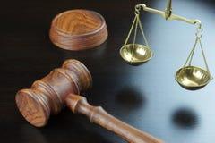 正义的法官惊堂木和标度在黑表上的 库存图片
