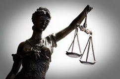 正义,更加黑暗的边缘古铜色雕象  图库摄影