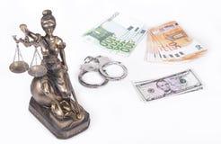正义Themis雕象与金钱欧元和美元的 贿款和罪行概念 图库摄影