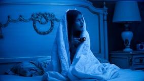 正在寻找妖怪的害怕的小女孩在黑暗的卧室 库存图片