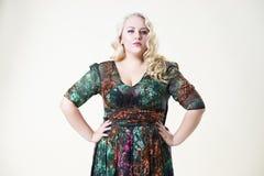 正大小时装模特儿,米黄背景的肥胖妇女,超重女性身体 库存照片