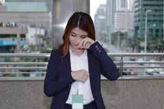 正式制服的沮丧的沮丧的年轻亚裔女商人哭泣在都市城市背景的 免版税图库摄影