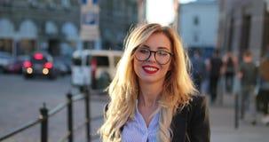 正式成套装备的和玻璃的步行沿着向下城市街道的后面观点的一名美丽的白肤金发的妇女,转向照相机 影视素材