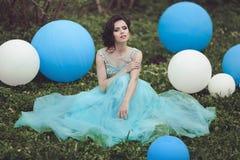 正式舞会的愉快的女孩与氦气气球 一件蓝色礼服的美丽的女孩毕业生坐草在a附近 免版税库存照片