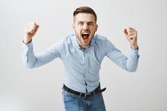 正式蓝色弯曲往照相机的衬衣和牛仔裤的上升感情兴奋的有关欧洲男性的上司叫喊和 库存照片