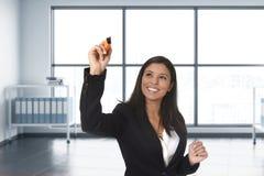 正式衣服文字的拉丁女商人与在无形的虚屏上的标志或委员会在现代办公室 免版税库存图片