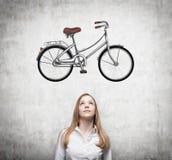 正式衣裳的一个女孩作梦关于一辆新的自行车 自行车的剪影在混凝土墙上被画 免版税库存照片