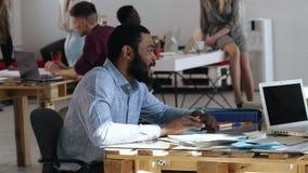 正式衬衣的愉快的年轻正面非洲人微笑对面试的坐在时髦现代顶楼办公室桌上 股票视频