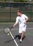 正手击球使男性球员摇摆网球 免版税库存图片