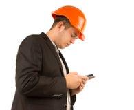 读正文消息的年轻工程师或建筑师 免版税库存照片