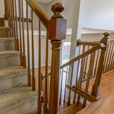 正方形与棕色扶手栏杆的覆盖着的楼梯在有发光的木地板的一个房子里面 免版税库存图片