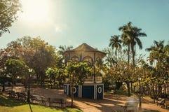 正方形老和五颜六色的眺望台在充分嫩绿的庭院的树中间,在São曼纽尔的一个明亮的晴天 免版税库存照片