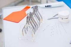 正牙医生牙齿套钳位和钳子和在工作表上的其他工具浮出水面 免版税库存图片