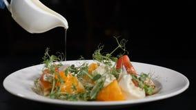 正确的食物概念 与橄榄油选矿的健康菜沙拉 拿着白色瓶子用橄榄的厨师特写镜头射击 股票录像