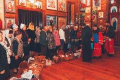 正统教士在一个木教会里奉献与复活节蛋糕和鸡蛋的圣水 免版税库存图片