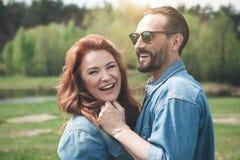 正面中年男人和妇女拥抱室外 免版税库存图片