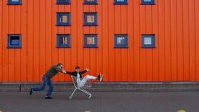 正面人在手推车滚动另一个人在商店,橙色背景,拷贝空间,慢动作附近 影视素材