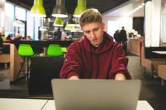 正面人研究在餐馆的背景的一台膝上型计算机 愉快的学生工作 免版税库存照片
