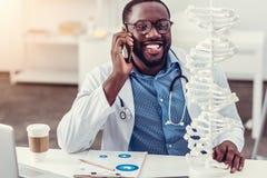 正面介意年轻医疗专业谈话在电话和微笑 免版税库存照片