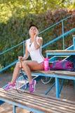 正面俏丽的女孩谈话在电话在体育场背景的羽毛球训练以后 繁忙的生活方式概念 库存图片