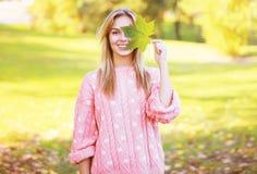 正面俏丽的妇女获得乐趣在晴朗的秋天 免版税库存图片