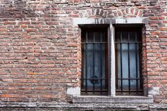正面图老砖门面两长方形窗口金属化保护 损坏的老建筑 Painted困厄了墙壁 库存照片