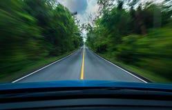 正面图蓝色驾车与在柏油路中部的最快速度有交通标志白色和黄线的  免版税库存图片