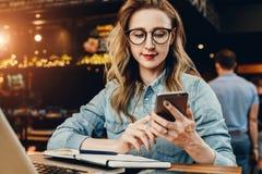 正面图 使用智能手机,年轻女实业家在咖啡店坐在计算机和笔记本前面的桌上, 免版税图库摄影