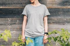 正面图 在灰色T恤杉打扮的年轻千福年的妇女是反对灰色木墙壁的立场 免版税库存图片