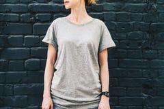 正面图 在灰色T恤杉打扮的年轻千福年的妇女是反对黑暗的砖墙的立场 免版税库存图片