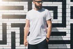 正面图 在白色T恤杉和太阳镜打扮的年轻有胡子的千福年的人是反对砖墙的立场 嘲笑 库存照片