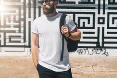 正面图 在白色T恤杉和太阳镜打扮的年轻有胡子的千福年的人是反对砖墙的立场 嘲笑 免版税库存图片