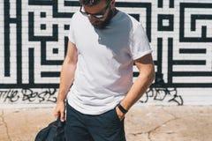 正面图 在白色T恤杉和太阳镜打扮的年轻有胡子的千福年的人是反对砖墙的立场 嘲笑 图库摄影