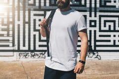 正面图 在白色T恤杉打扮的年轻有胡子的千福年的人是反对砖墙的立场 嘲笑 免版税库存图片