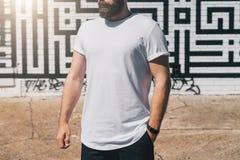 正面图 在白色T恤杉打扮的年轻有胡子的千福年的人是反对砖墙的立场 嘲笑 免版税库存照片