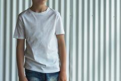 正面图 在白色T恤杉打扮的年轻行家男孩是室内立场反对白色墙壁 嘲笑 商标的空间 免版税库存照片