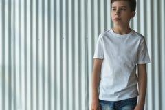正面图 在白色T恤杉打扮的年轻行家男孩是室内立场反对白色墙壁 嘲笑 商标的空间 免版税库存图片